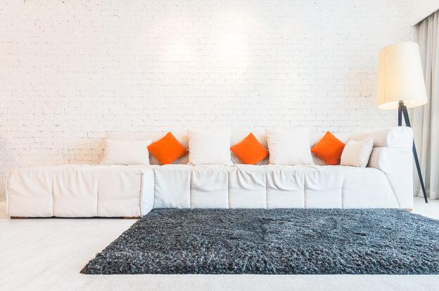 Foto de tapete e sofa representando dicas de como recuperar a maciez do tapete