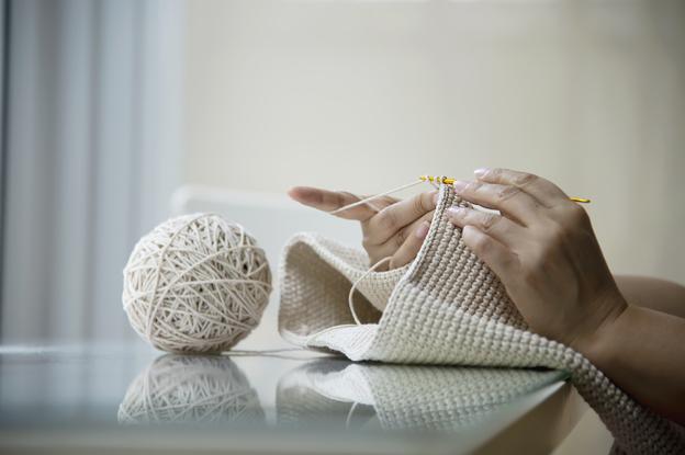 mulher tricotando representando como lavar tapete de crochê