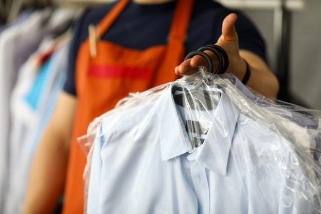 homem segurando peças de roupas representando a lavanderia preços