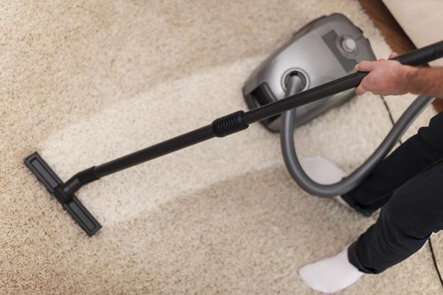 pessoa limpando com aspirador representando como limpar carpete
