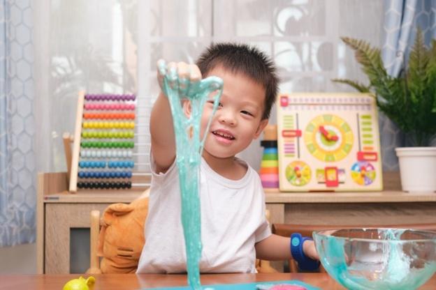 criança brincando com slime representando como tirar amoeba do tapete