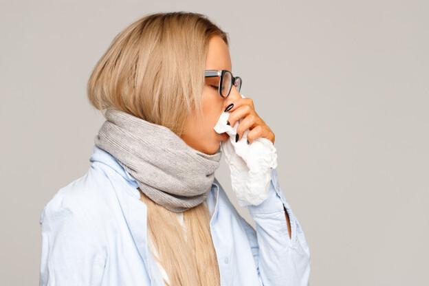 mulher assoando o nariz por não ter tapete antialérgico na sala