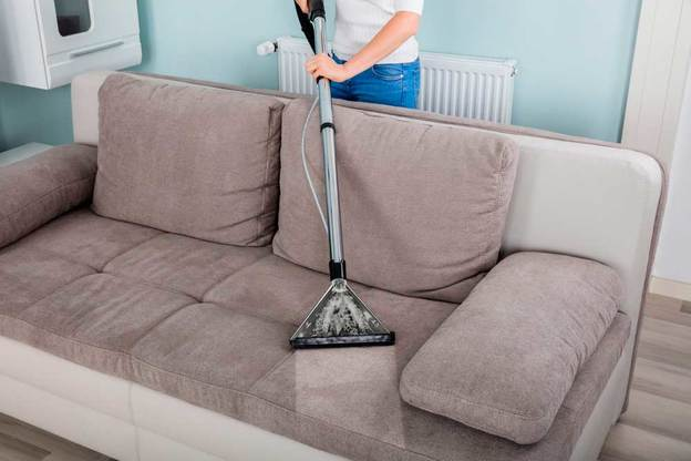 homem aspirando representando como limpar sofá de camurça