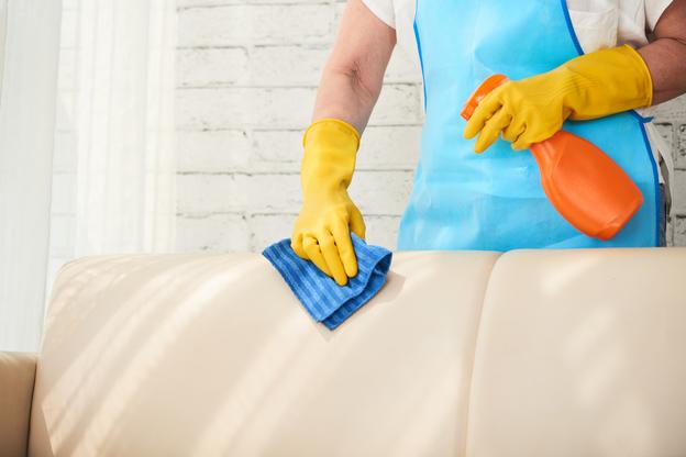 homem passando pano representando Como limpar sofás de pele